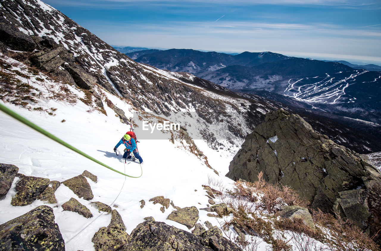 HIGH ANGLE VIEW OF PERSON RIDING ON SNOWCAPPED MOUNTAIN