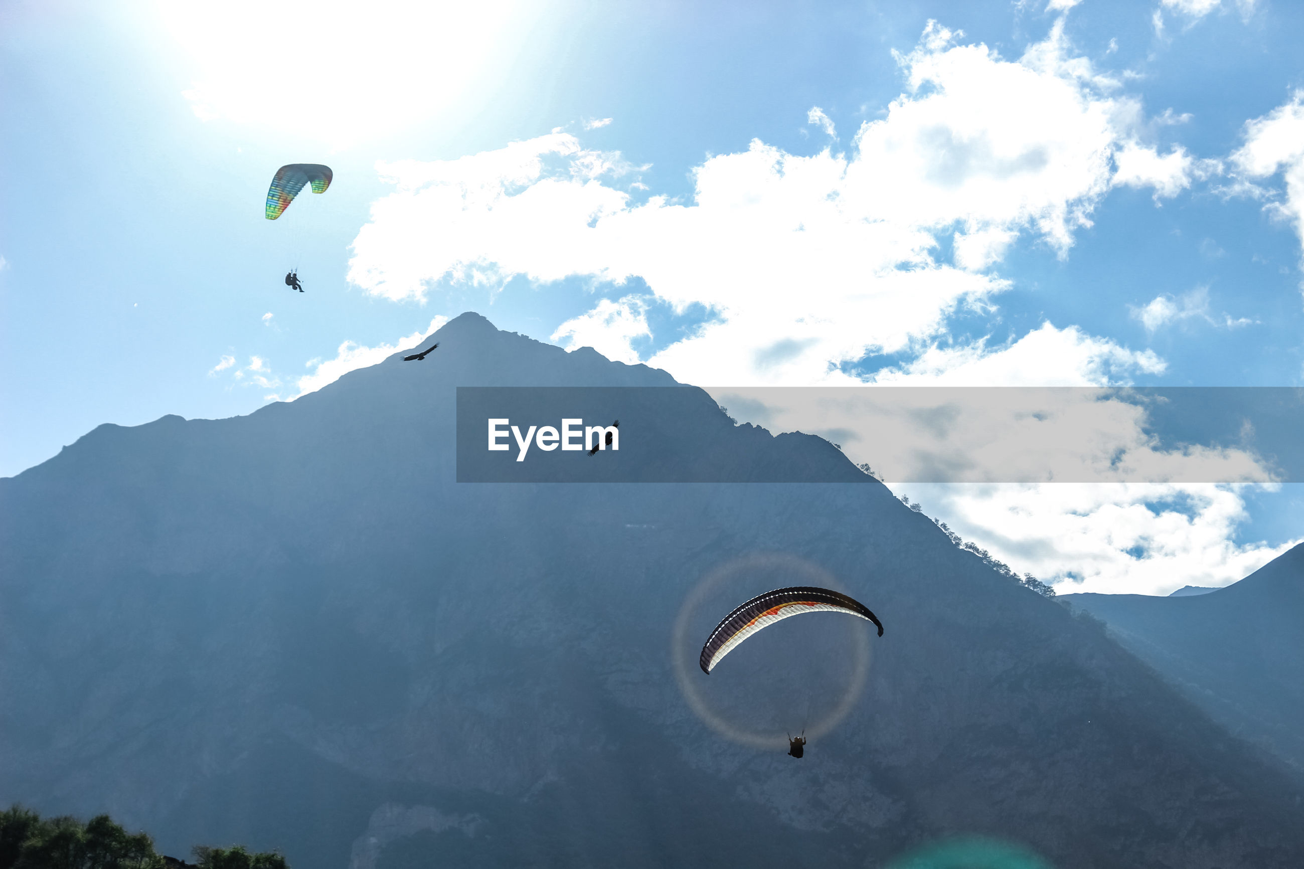 Person paragliding over mountain against sky
