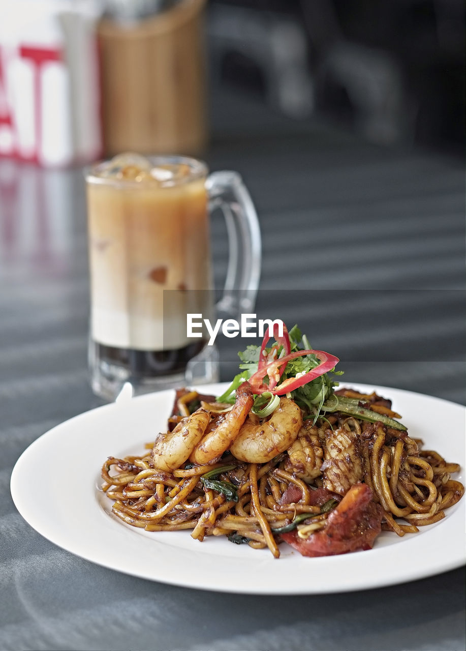 Close-Up Of Mie Goreng With Iced Coffee On Table