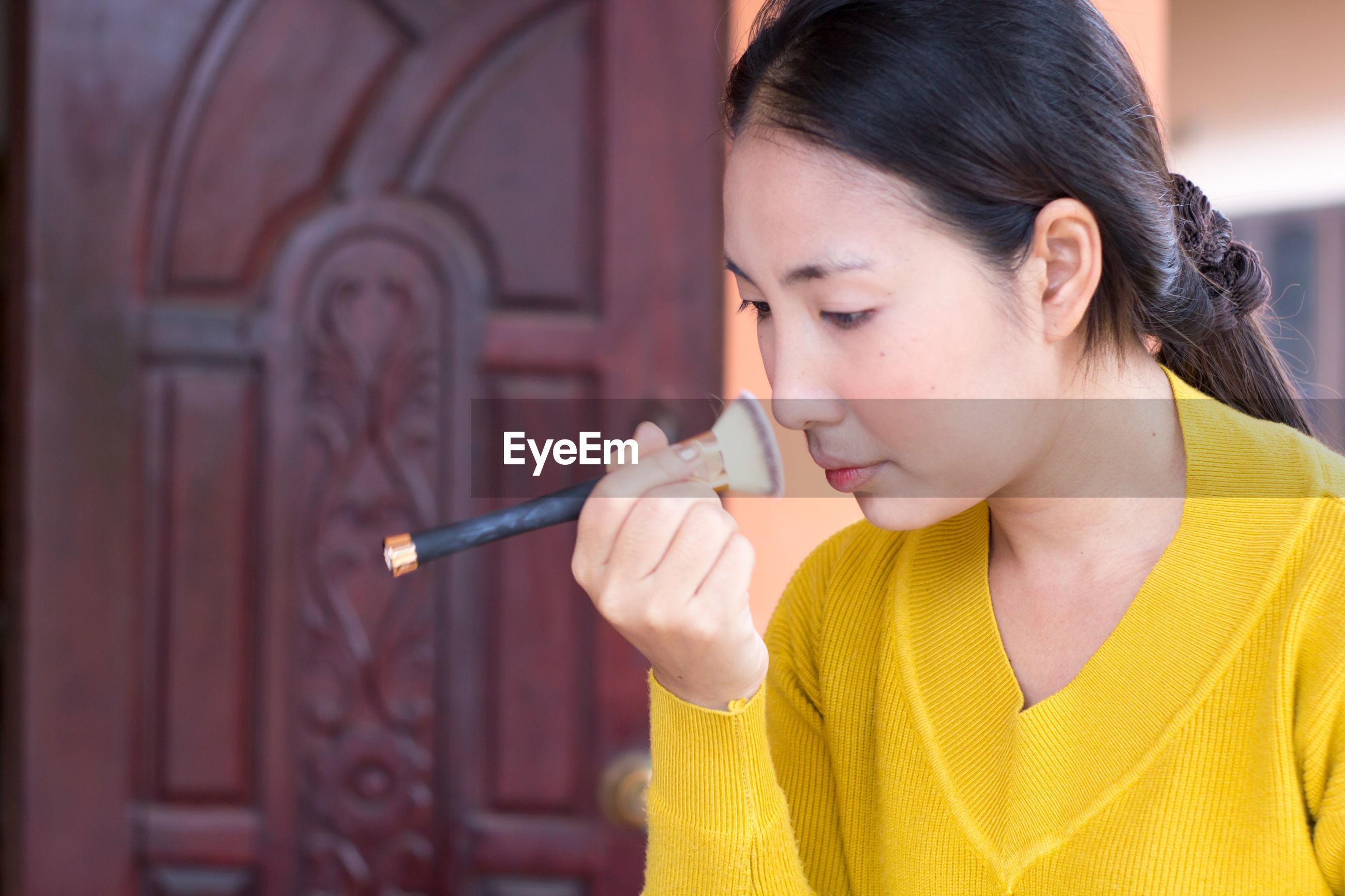 Close-up of woman applying make-up at home