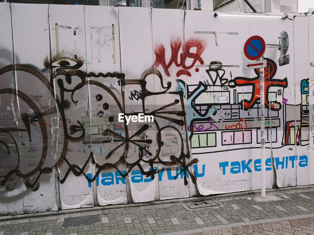 GRAFFITI ON WALL BY FOOTPATH IN CITY