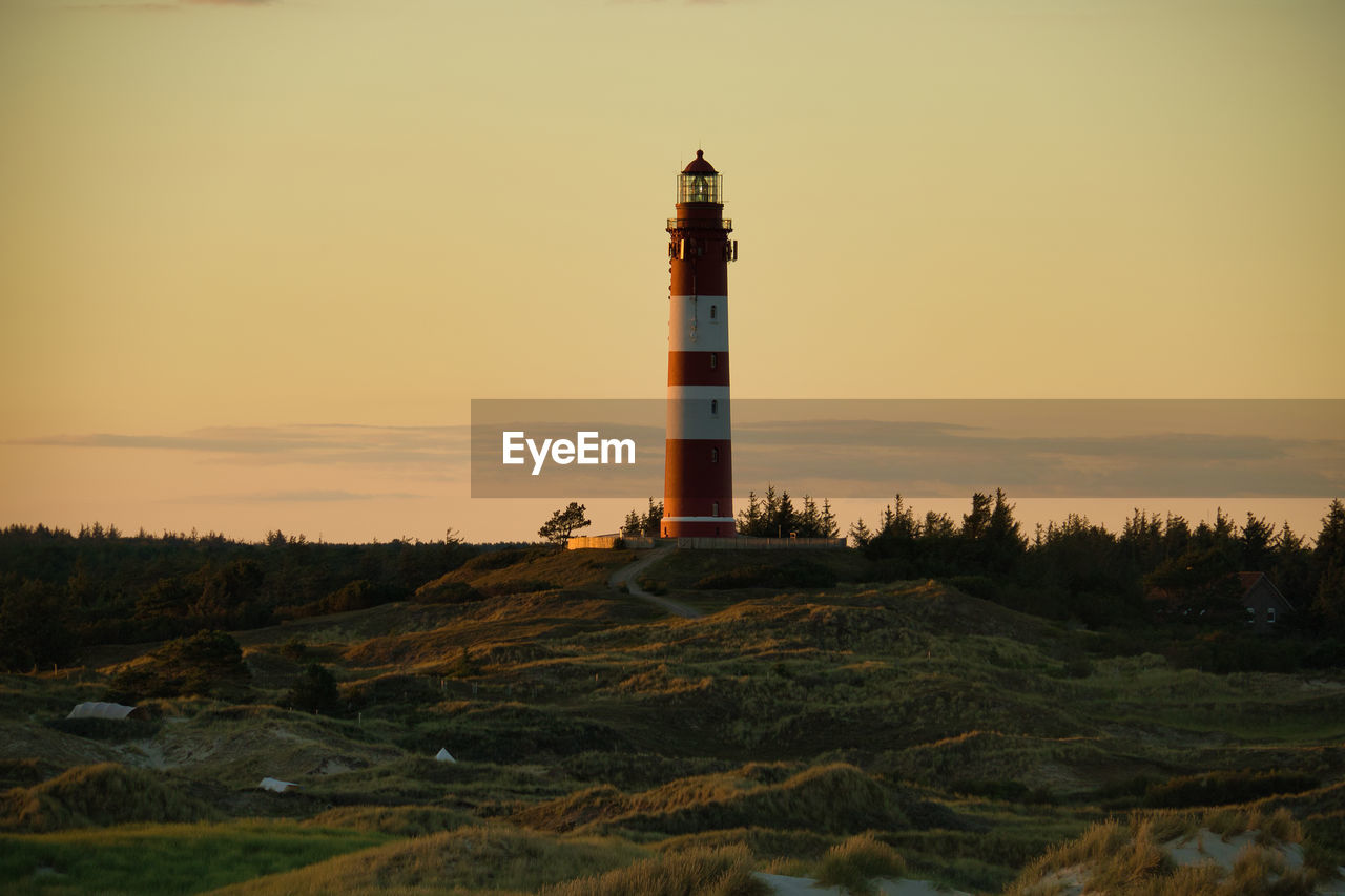Lighthouse on field by building against sky during sunset
