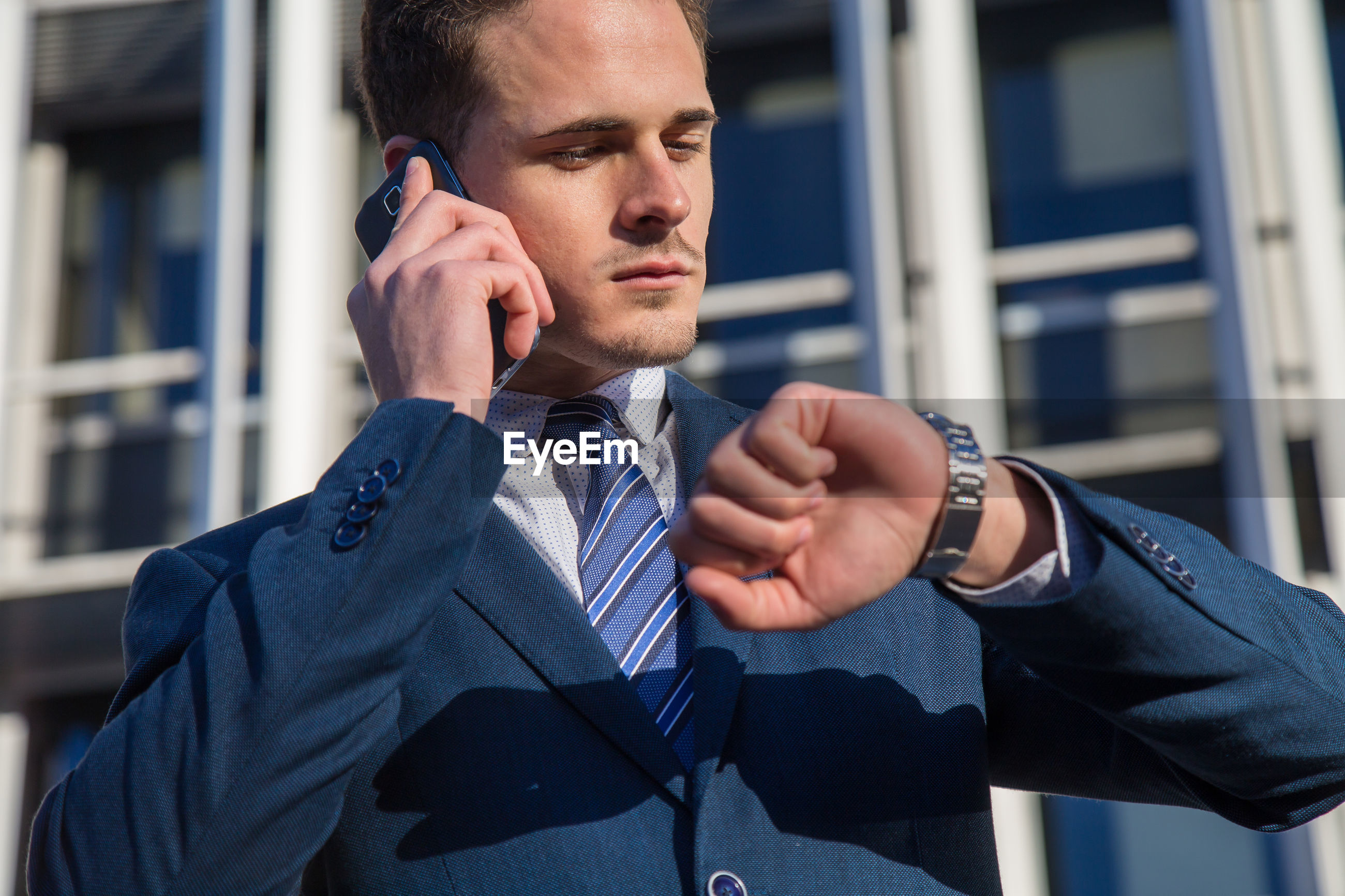 Low angle view of businessman talking on phone while checking time in city