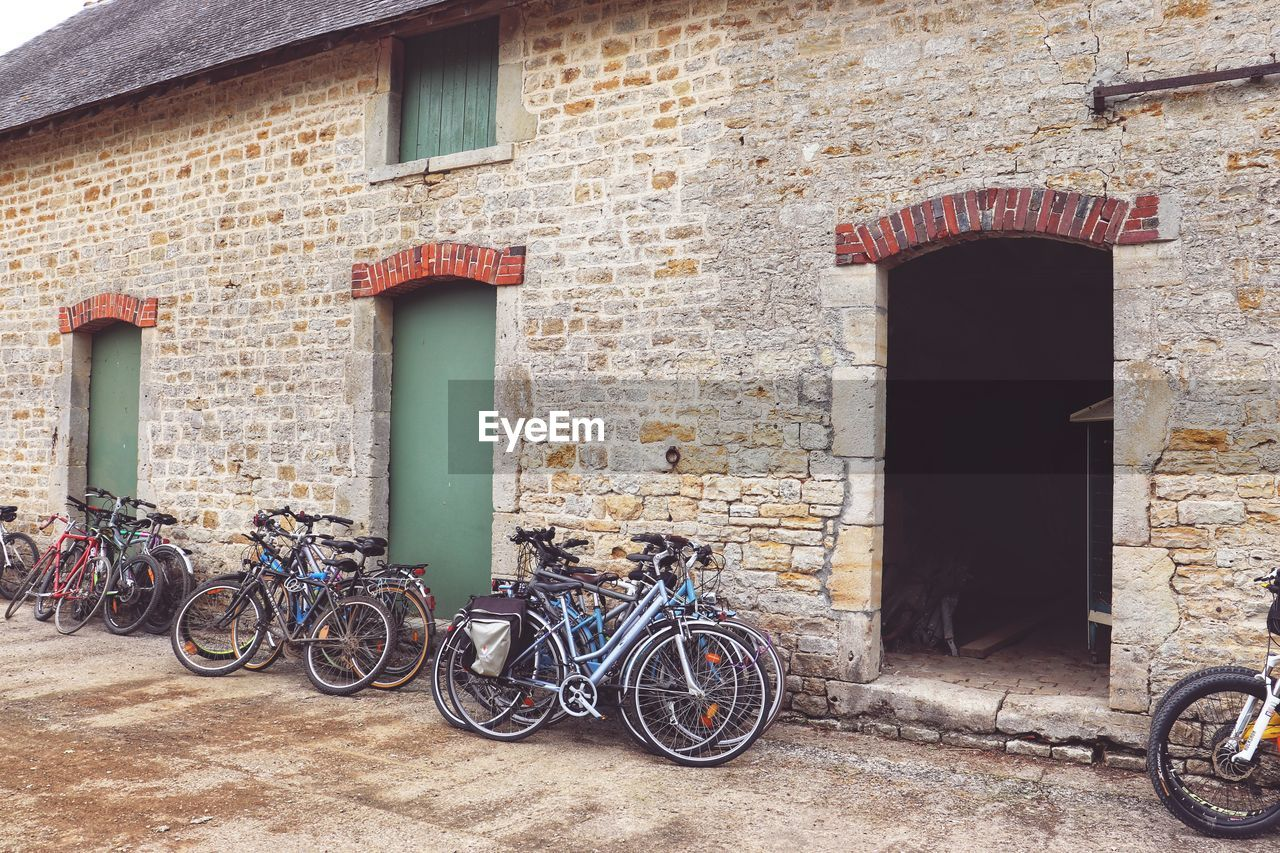 architecture, built structure, building exterior, building, transportation, bicycle, wall, brick wall, land vehicle, stationary, entrance, door, mode of transportation, brick, day, no people, parking, outdoors, window, wall - building feature
