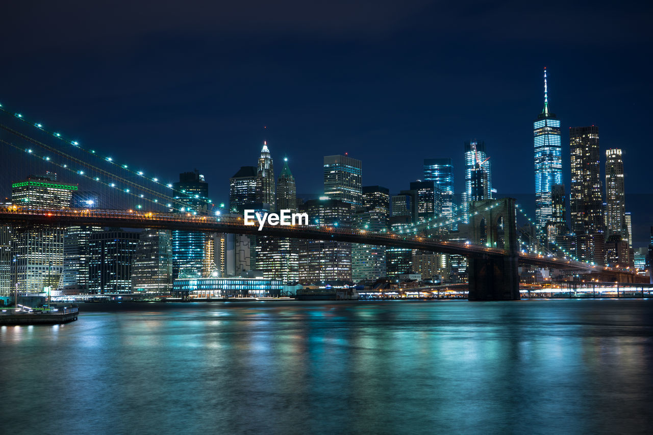 Illuminated Brooklyn Bridge Over River Against Buildings At Night