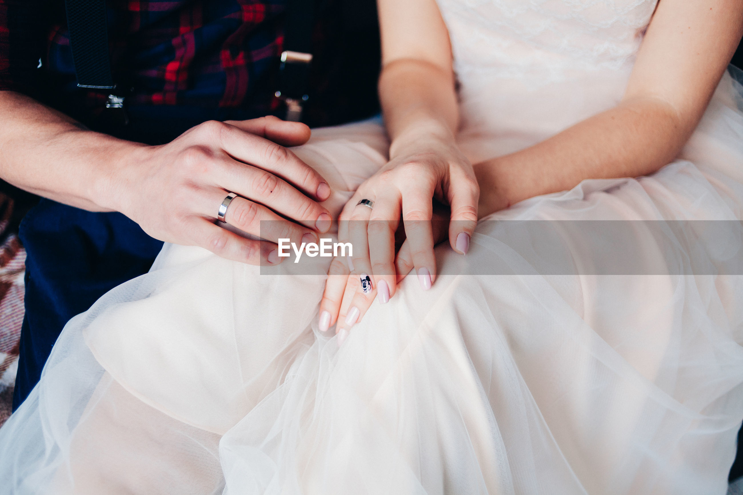 Midsection of bride and groom in wedding dress sitting on bed
