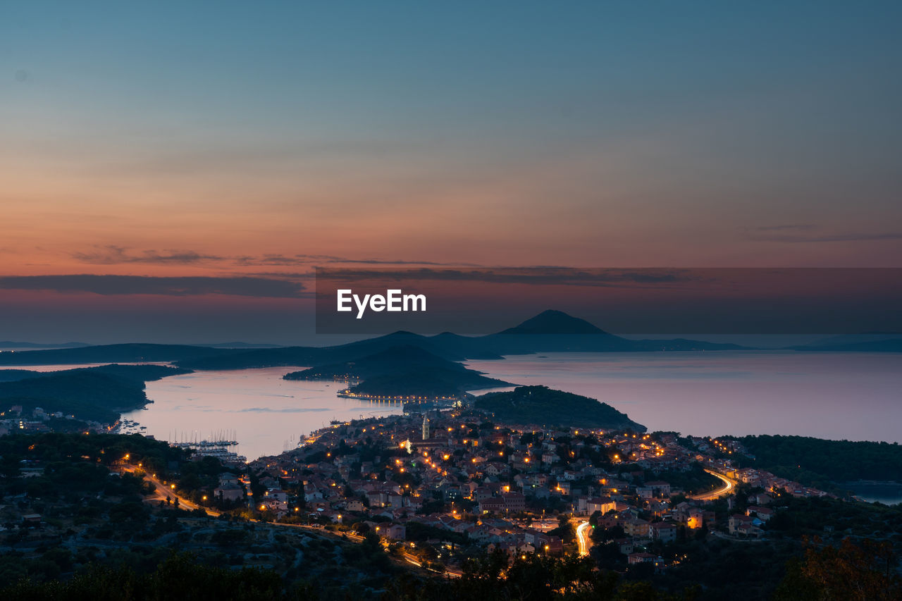 High Angle View Of Illuminated Cityscape By Sea Against Sky During Sunset