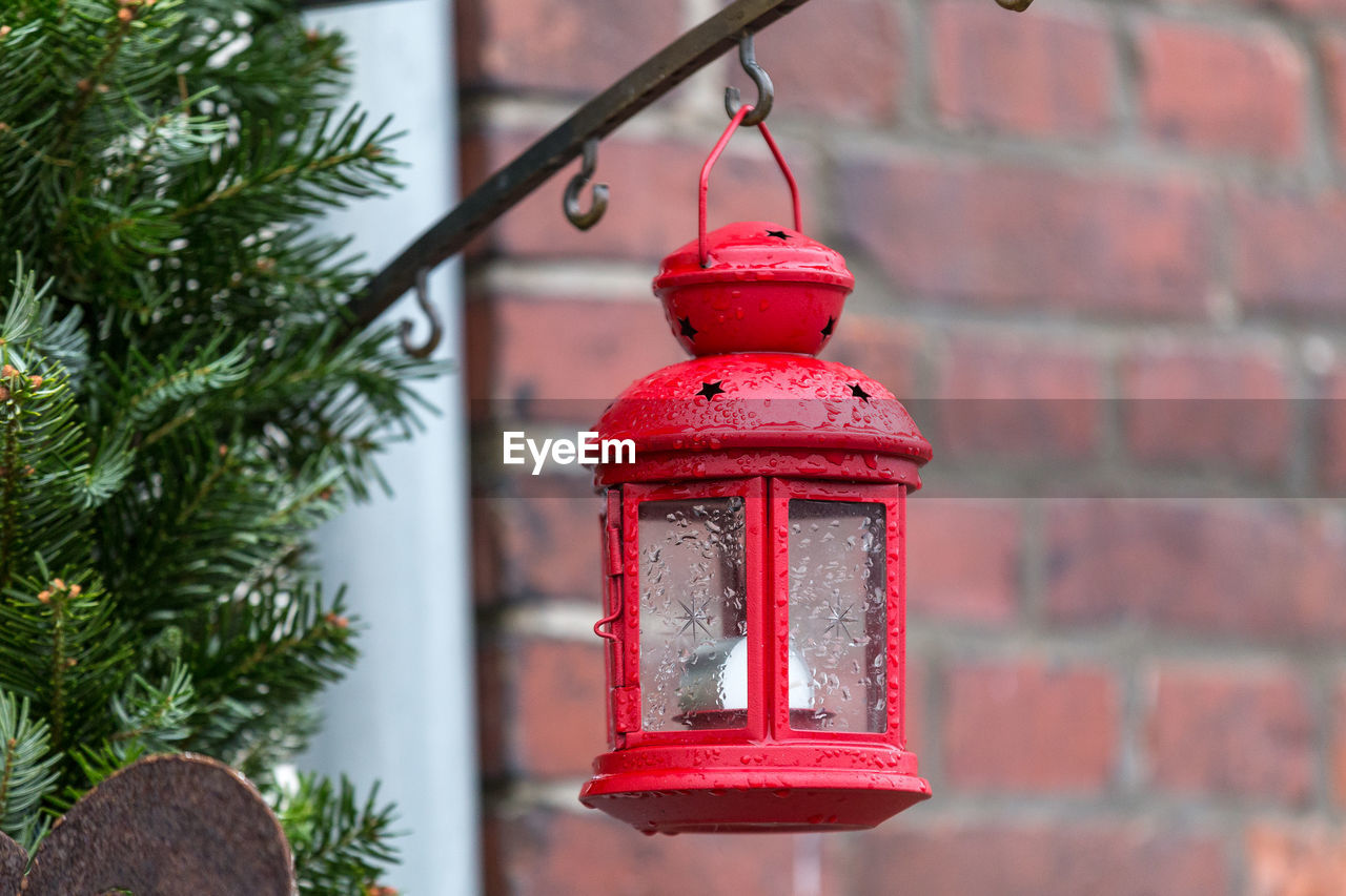 red, focus on foreground, hanging, lighting equipment, lantern, day, built structure, architecture, wall - building feature, no people, outdoors, close-up, metal, brick, wall, bell, building exterior, brick wall, tree, electric lamp