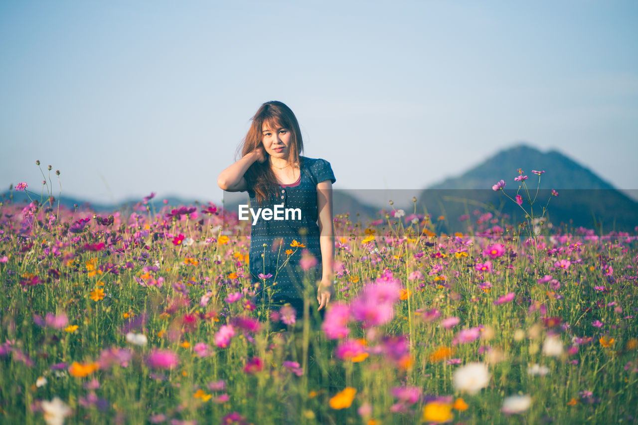 Woman Standing Amidst Flowering Plants On Field Against Sky