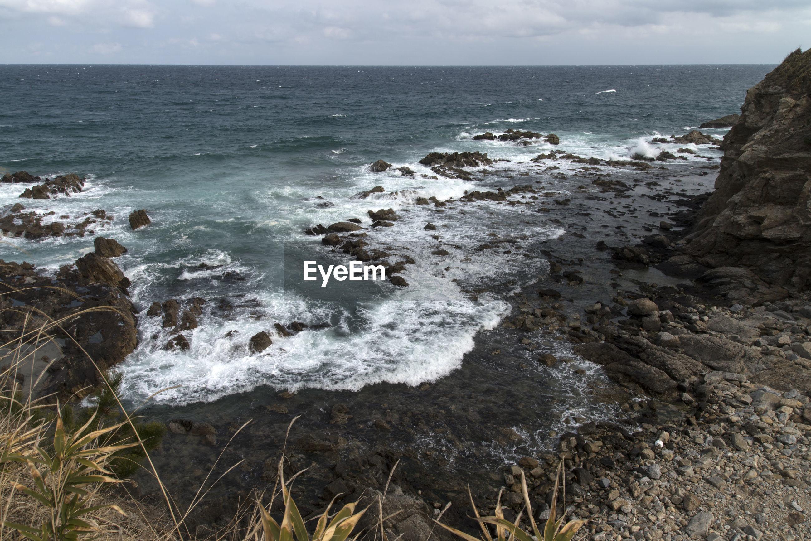 High angle view of sea waves splashing on rocks at shore