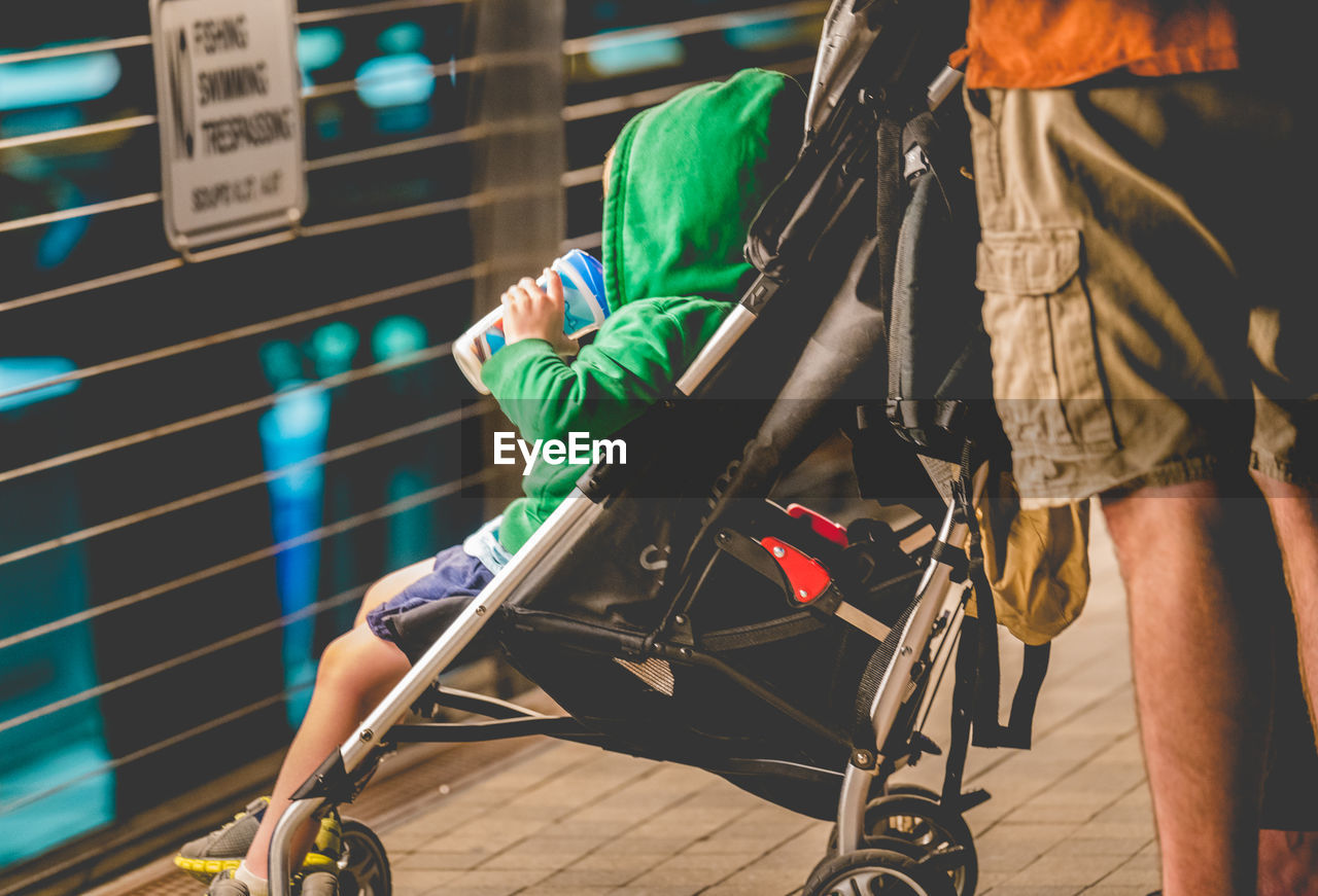 Midsection Of Man Standing By Son Sitting In Baby Stroller
