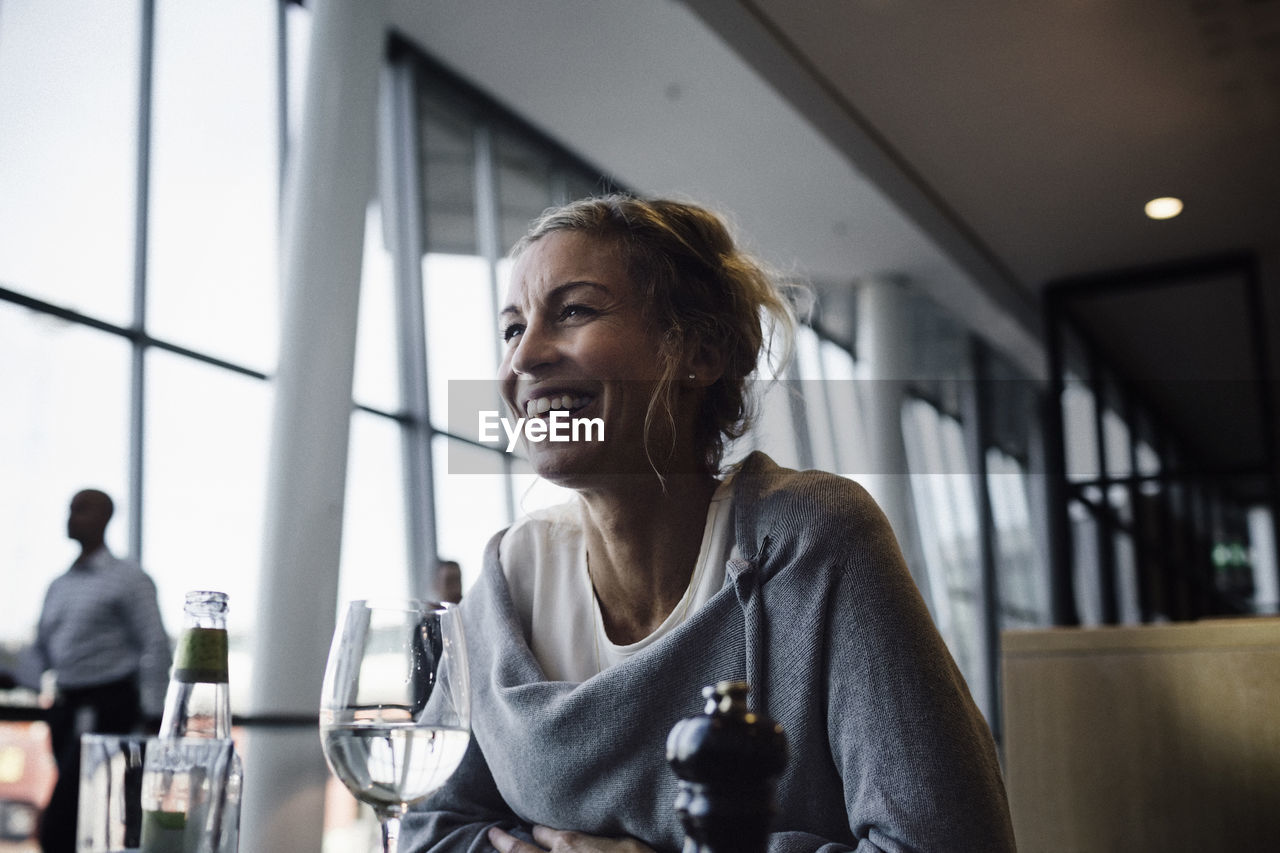 real people, indoors, smiling, looking away, women, one person, business, drink, table, refreshment, sitting, food and drink, restaurant, focus on foreground, headshot, lifestyles, window, adult, portrait, glass