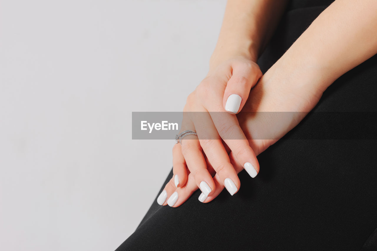 Midsection Of Woman With White Nail Polishes With Gray Background