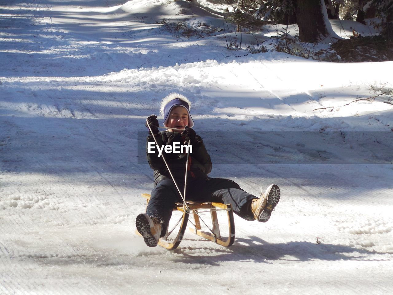 Boy riding sled on snow