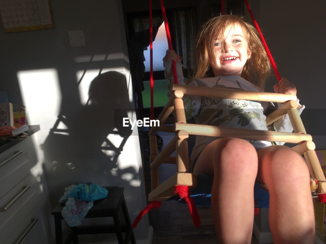 Cheerful girl on swing at home