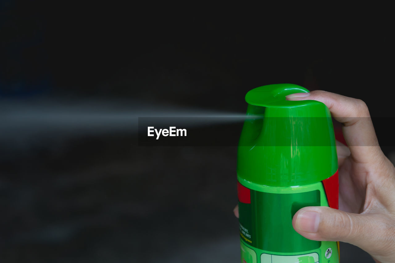 Close-up of hand holding spraying bottle
