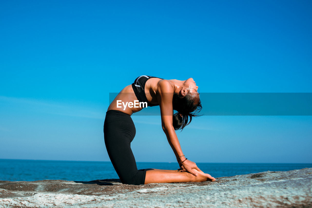 Woman Practicing Yoga At Beach Against Sky
