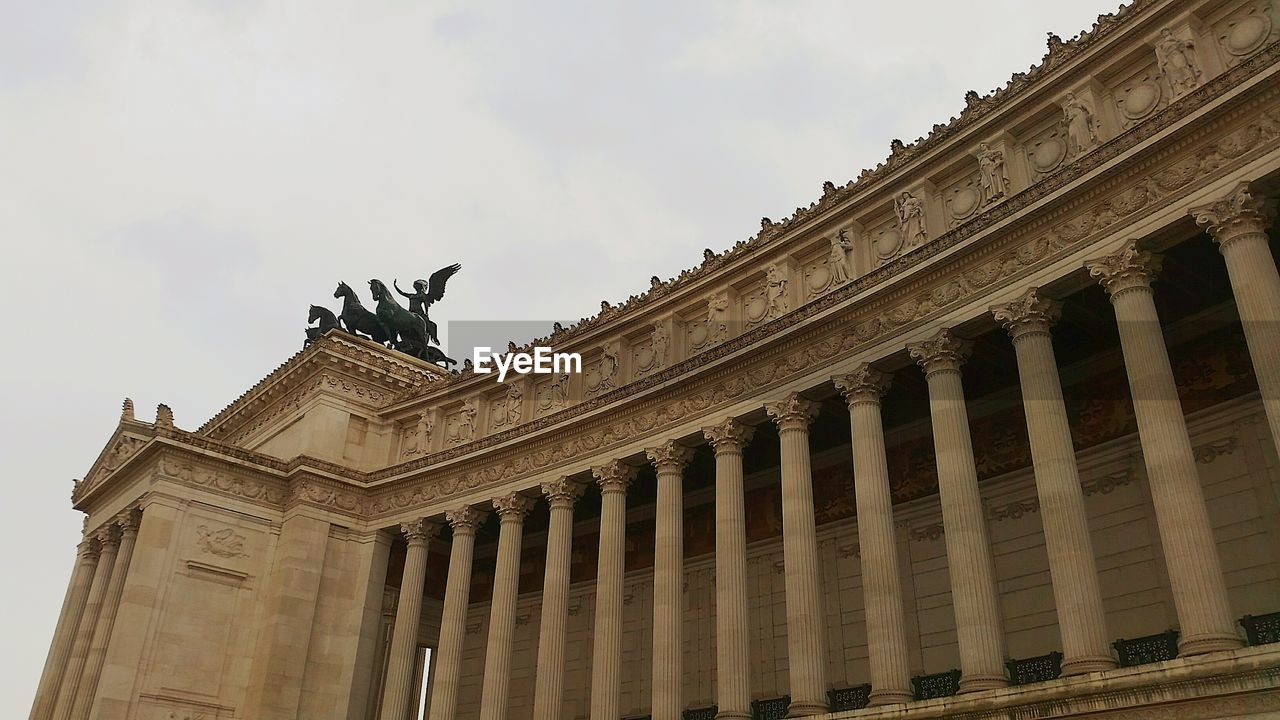 architecture, architectural column, statue, built structure, building exterior, sculpture, history, low angle view, animal representation, sky, travel destinations, outdoors, day, cloud - sky, no people, city