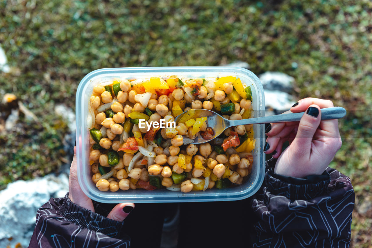 HIGH ANGLE VIEW OF PERSON HAND HOLDING FOOD