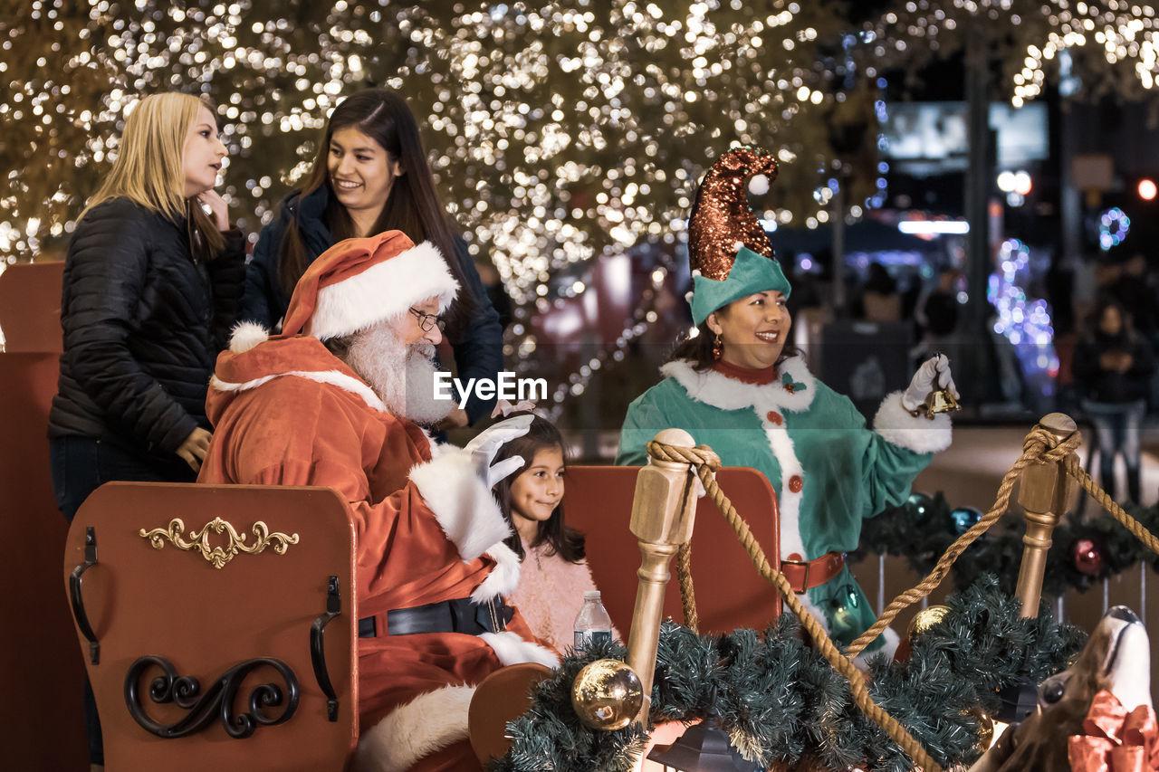 celebration, group of people, christmas, togetherness, women, sitting, females, holiday, christmas tree, adult, young women, smiling, emotion, decoration, males, illuminated, mammal, men