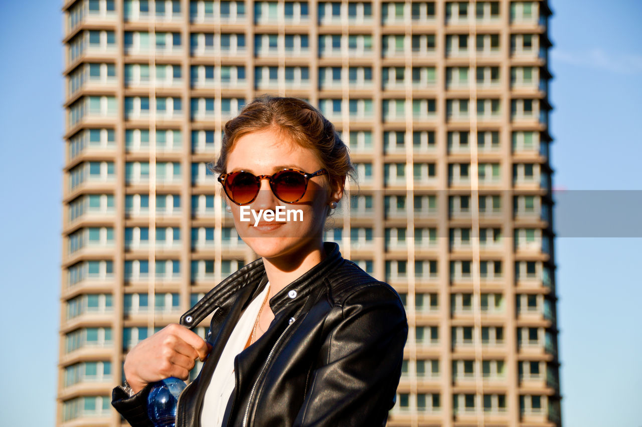 Portrait Of Young Woman In Sunglasses Standing By Building In City