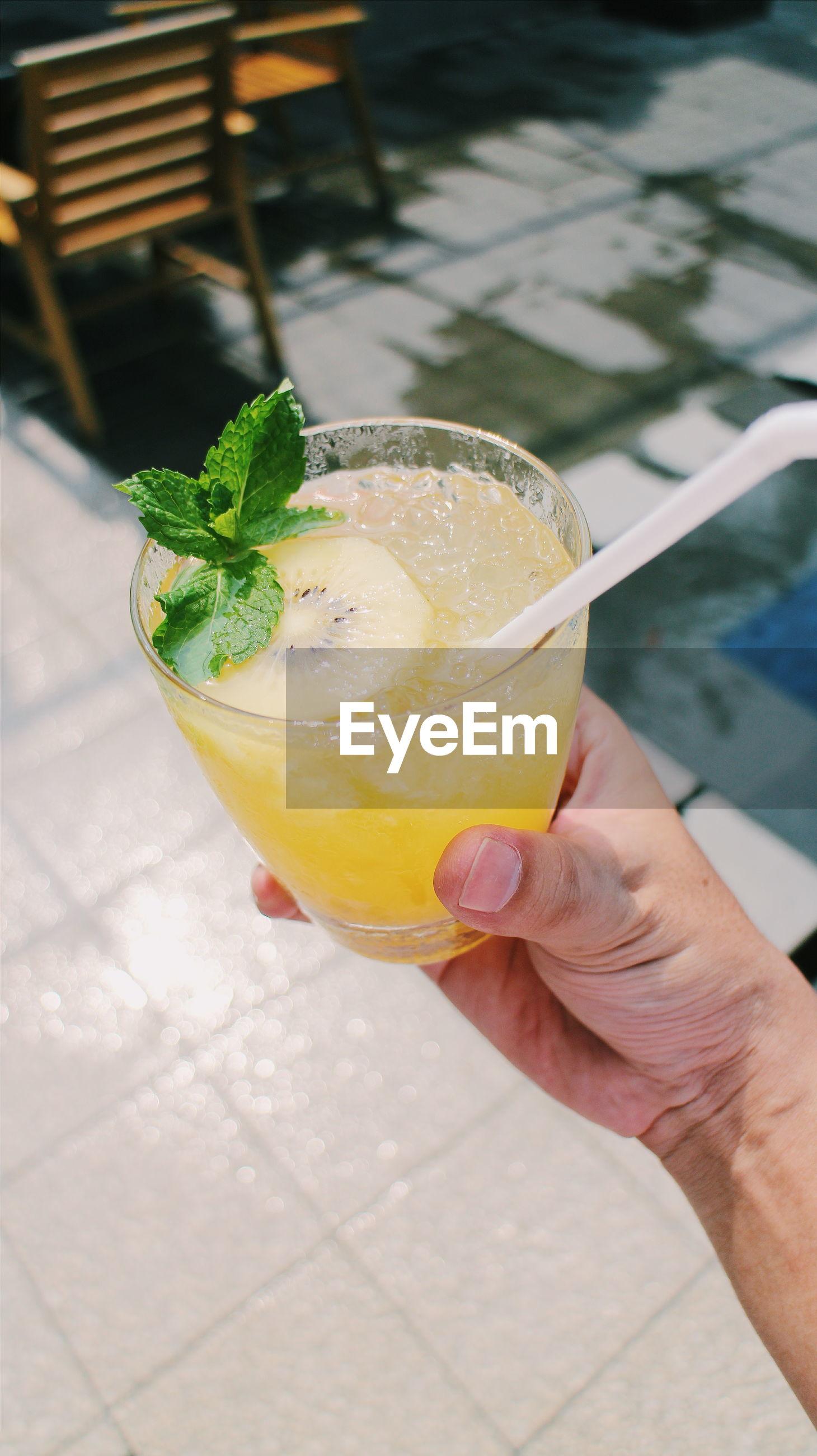 Cropped image of hand holding lemon juice