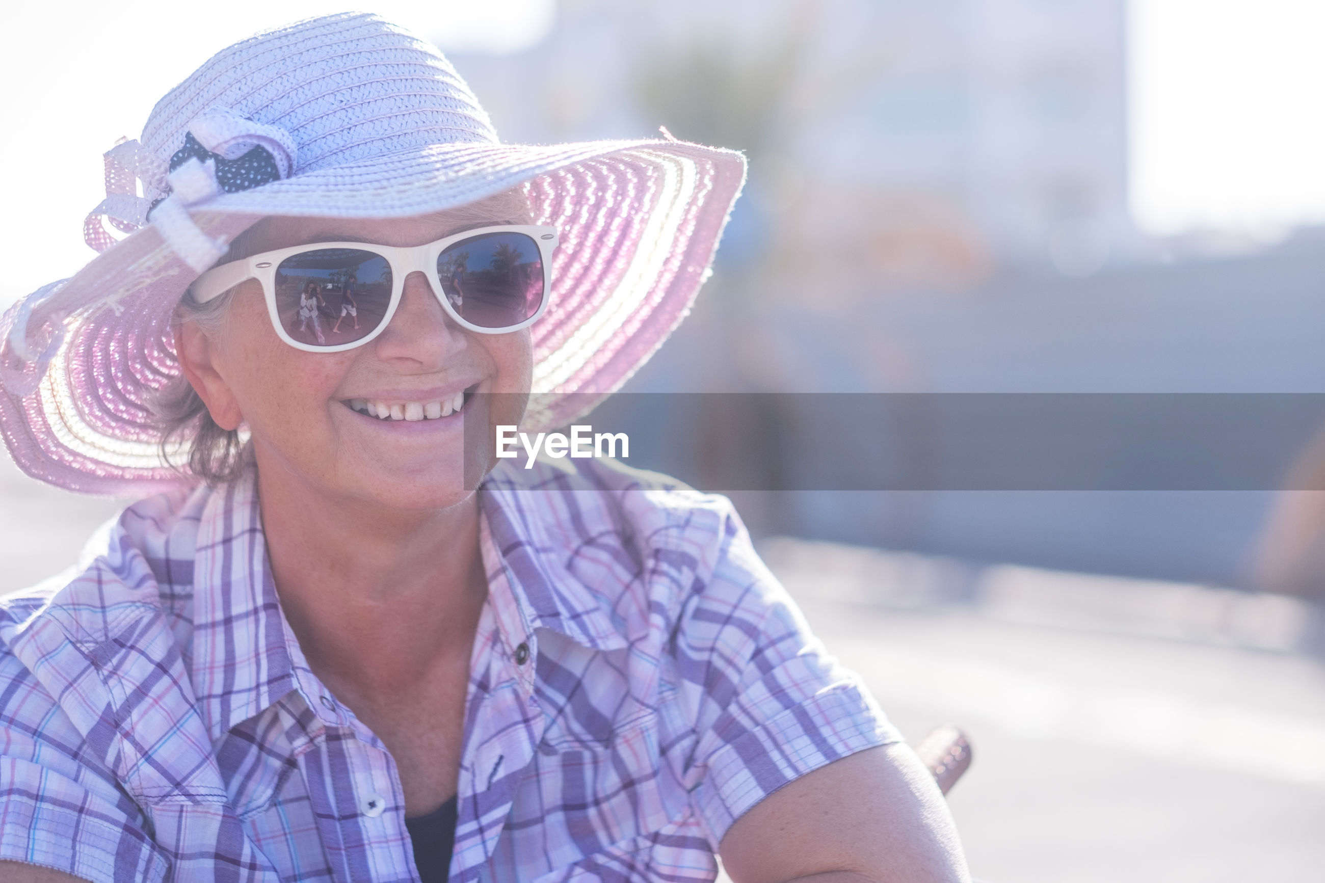 Smiling senior woman wearing sunglasses and hat outdoor