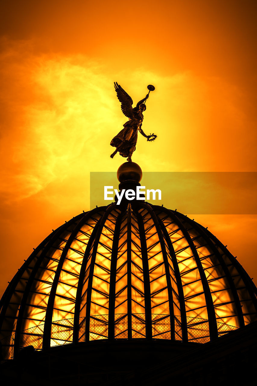 sunset, sky, orange color, art and craft, sculpture, statue, representation, cloud - sky, no people, nature, low angle view, human representation, architecture, silhouette, creativity, angel, outdoors, built structure, travel destinations, male likeness