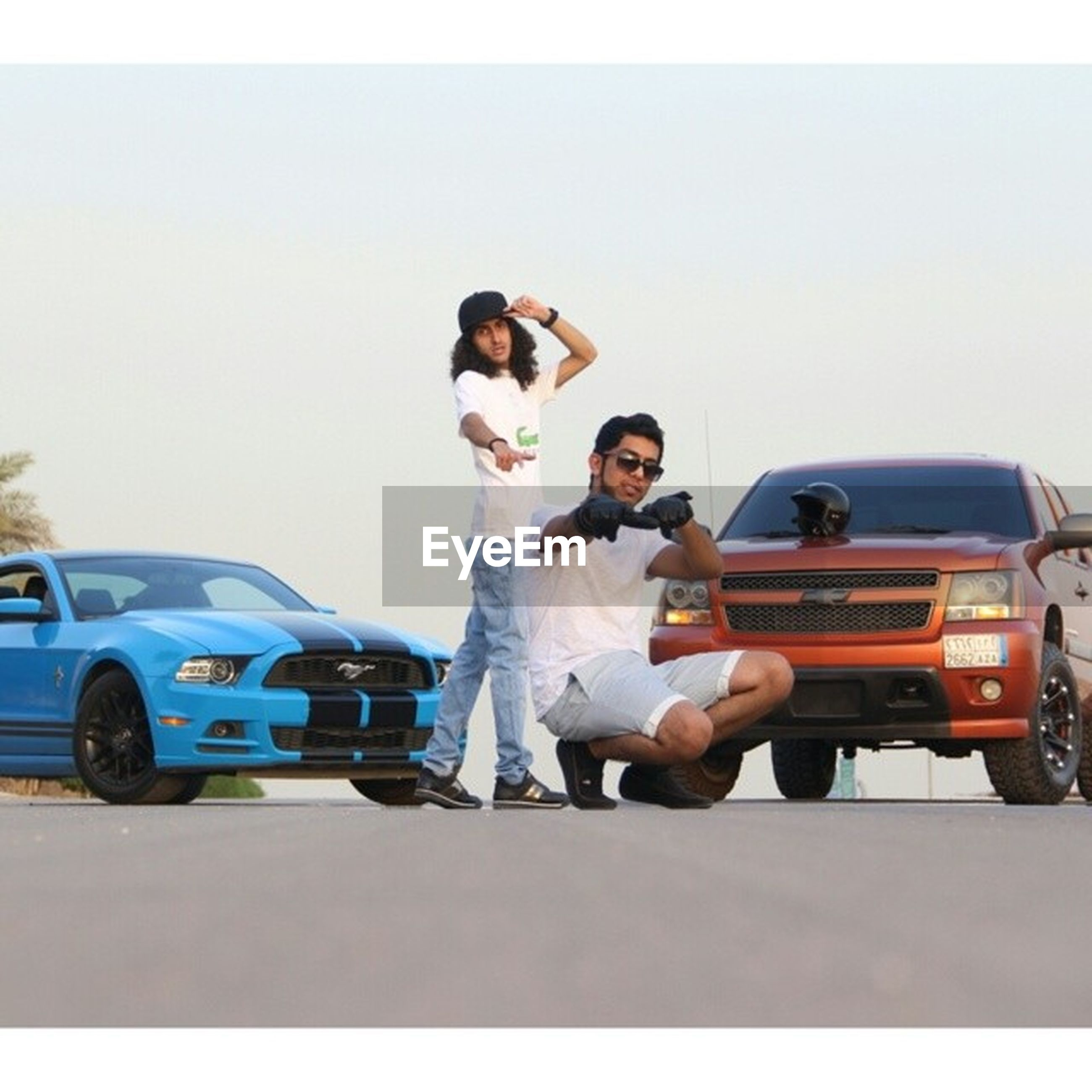 lifestyles, leisure activity, transportation, land vehicle, mode of transport, casual clothing, men, car, young adult, holding, full length, young men, person, clear sky, togetherness, photography themes, front view