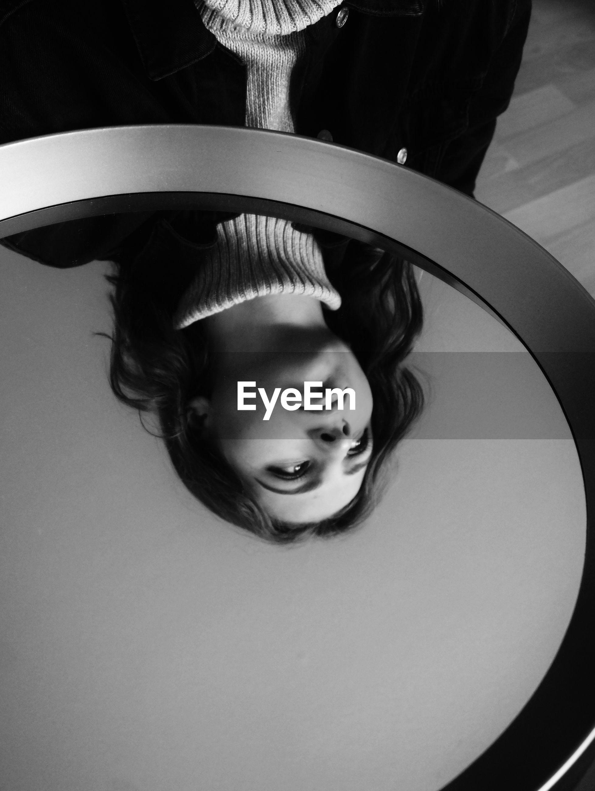 High angle view of woman reflection on glass table