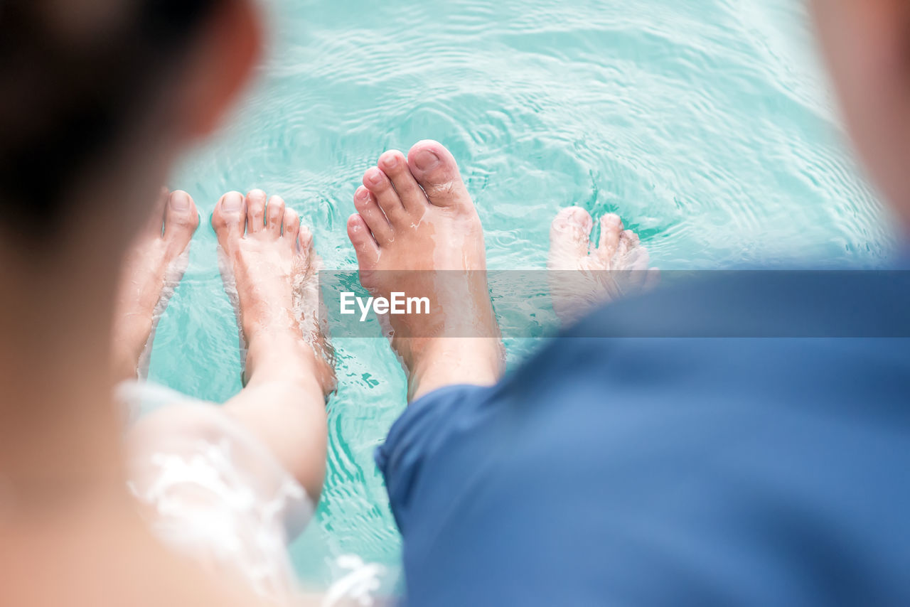 Low section of couple relaxing at edge of swimming pool