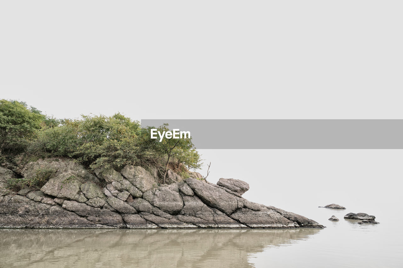 water, copy space, tree, waterfront, beauty in nature, tranquility, nature, plant, rock, scenics - nature, no people, tranquil scene, clear sky, rock - object, sky, solid, reflection, day, lake, outdoors