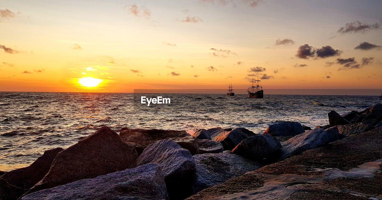 sunset, water, sky, sea, rock, rock - object, scenics - nature, solid, beauty in nature, beach, horizon, horizon over water, land, orange color, cloud - sky, tranquility, tranquil scene, nature, idyllic, sun, no people, outdoors, groyne, rocky coastline