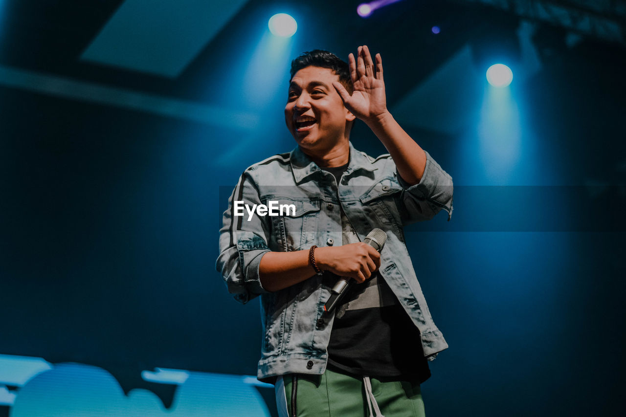 one person, front view, standing, illuminated, three quarter length, happiness, smiling, indoors, real people, young adult, stage, young men, stage - performance space, arts culture and entertainment, casual clothing, enjoyment, night, lifestyles, performing arts event, nightlife, arms raised, concert, light