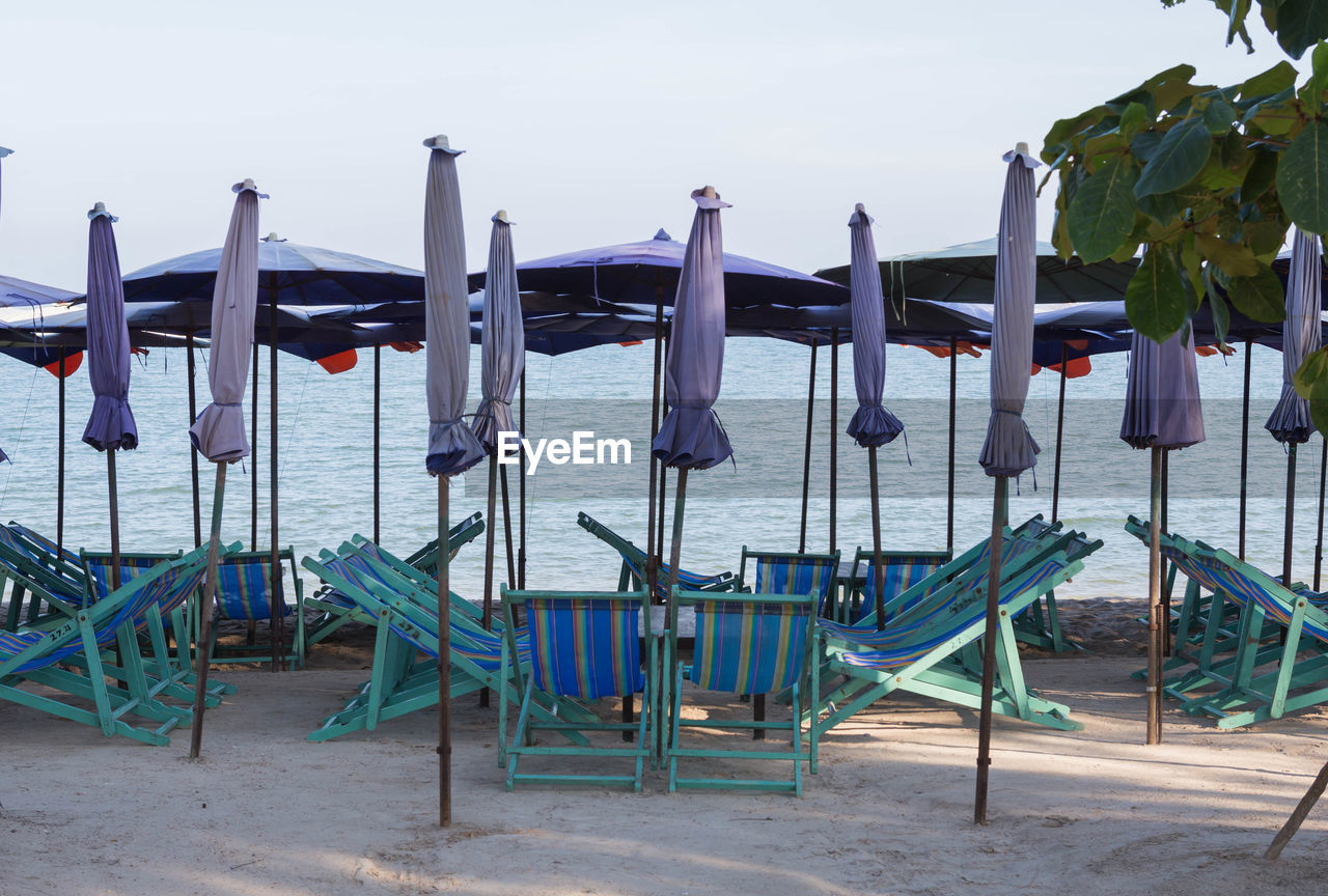 Lounge chairs and parasols at beach against sky