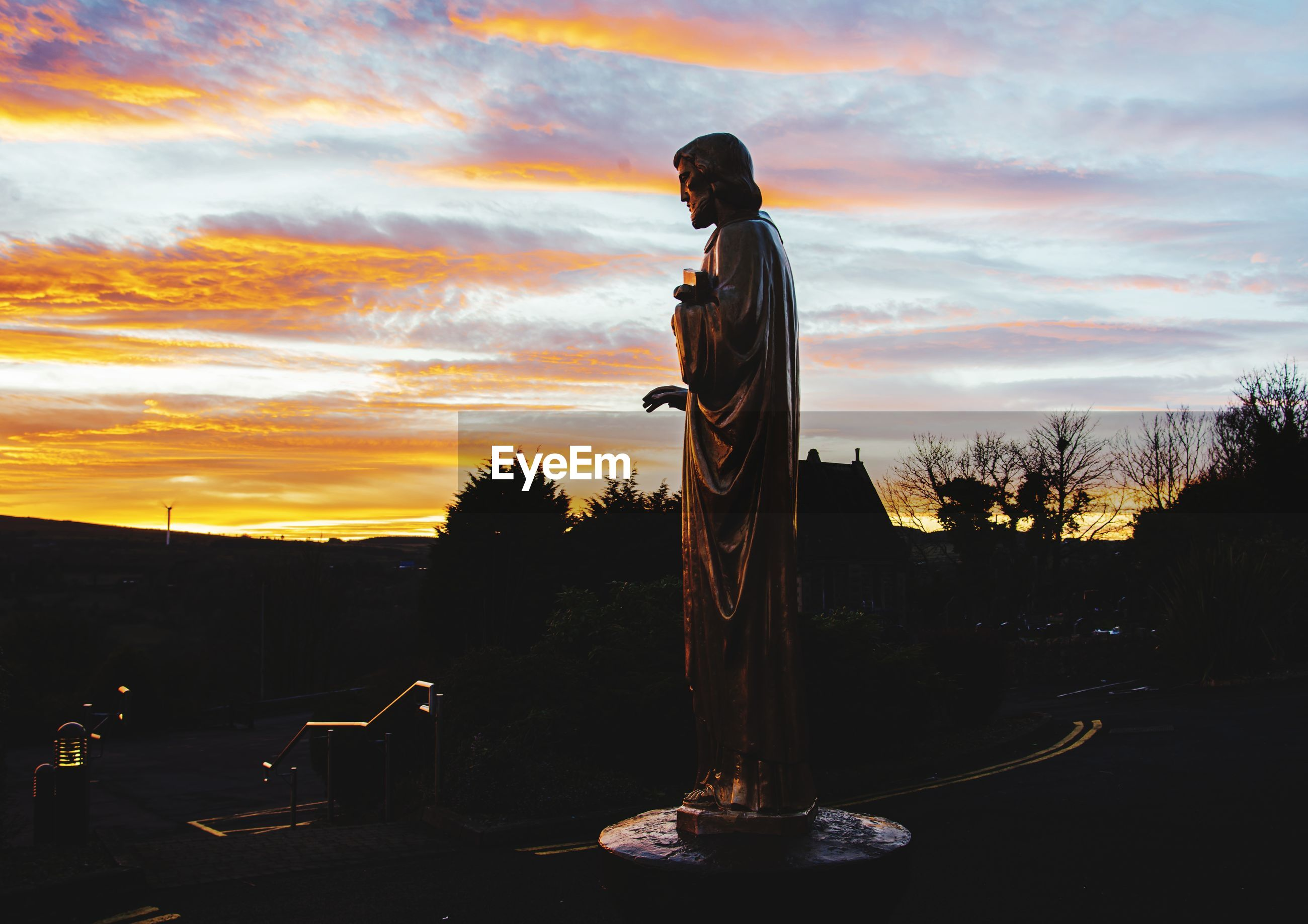 Side view of man standing by sculpture against orange sky