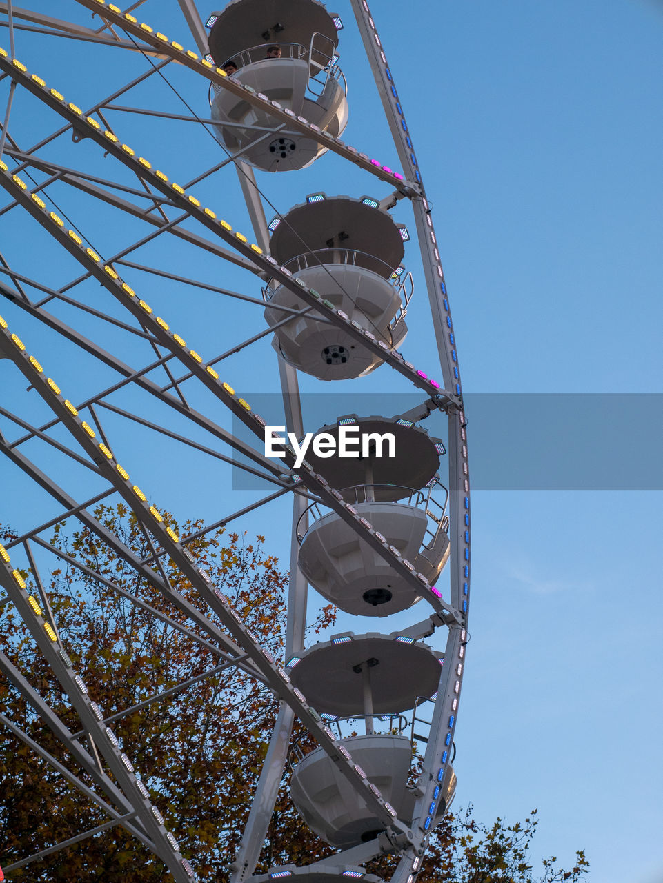 low angle view, sky, amusement park, amusement park ride, nature, day, ferris wheel, metal, no people, built structure, arts culture and entertainment, clear sky, architecture, outdoors, sunlight, blue, technology, plant, tree, fun