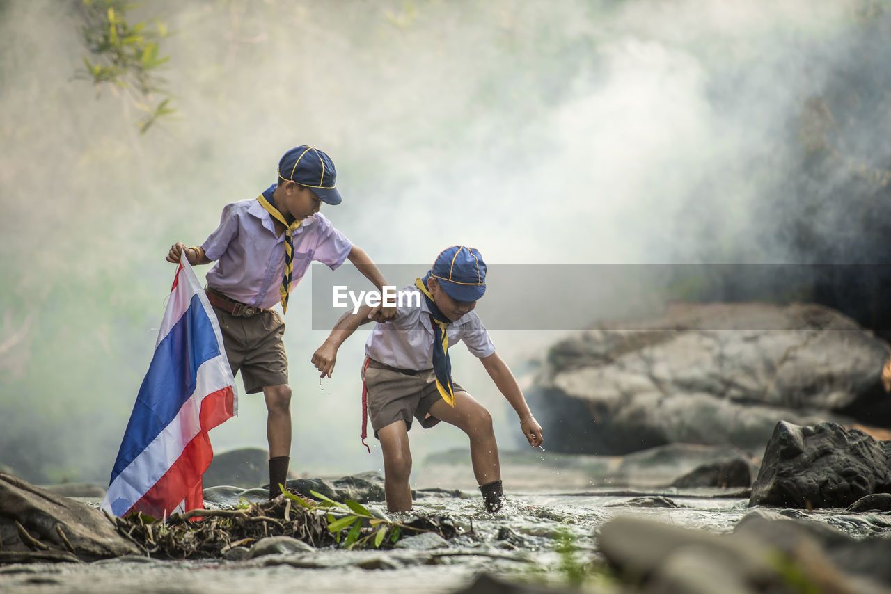 Students Wearing Uniform While Walking In Stream At Forest