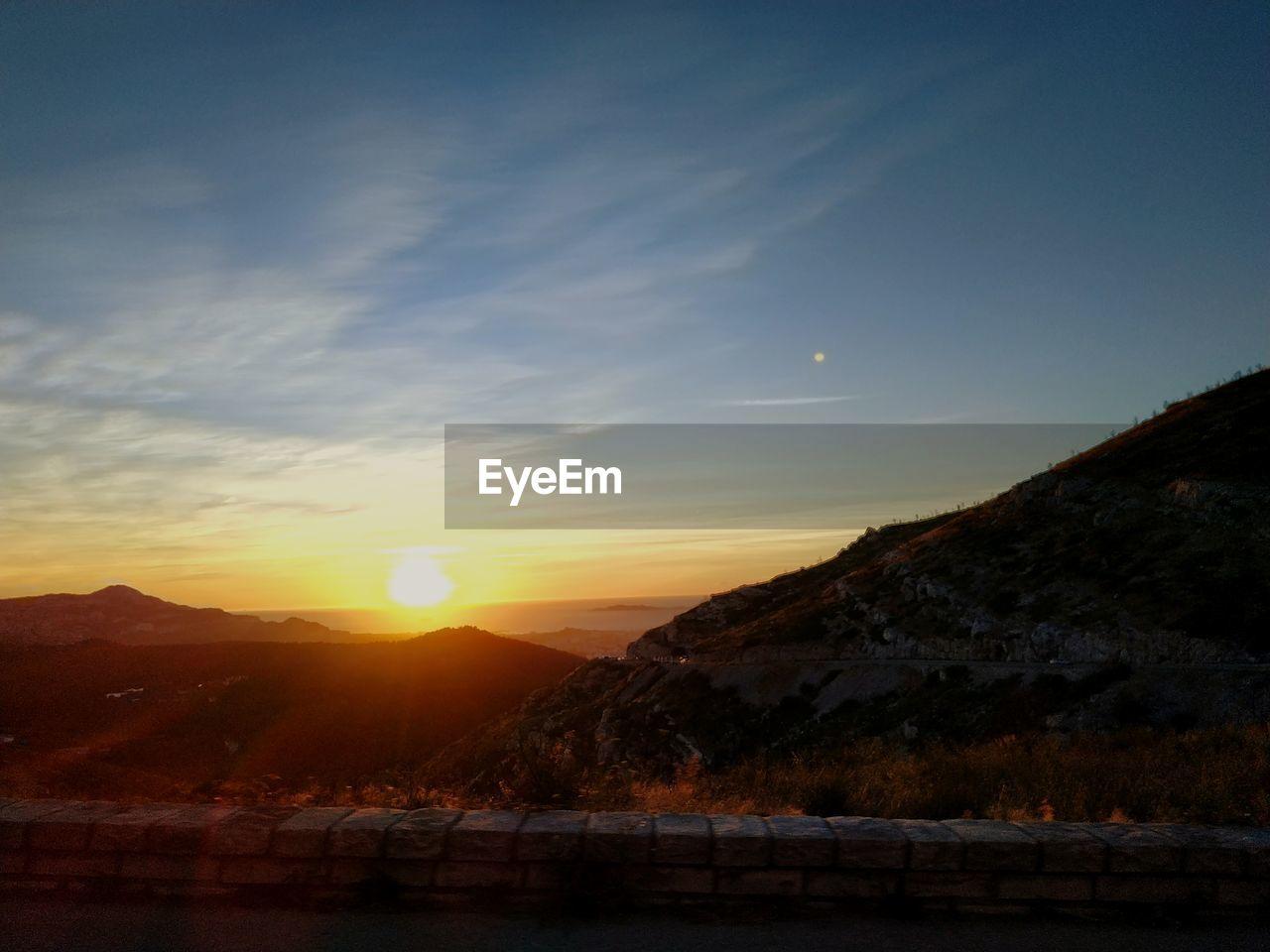 sky, sunset, mountain, beauty in nature, scenics - nature, tranquility, tranquil scene, sun, nature, water, no people, sunlight, orange color, mountain range, environment, cloud - sky, idyllic, outdoors, lake, lens flare, bright