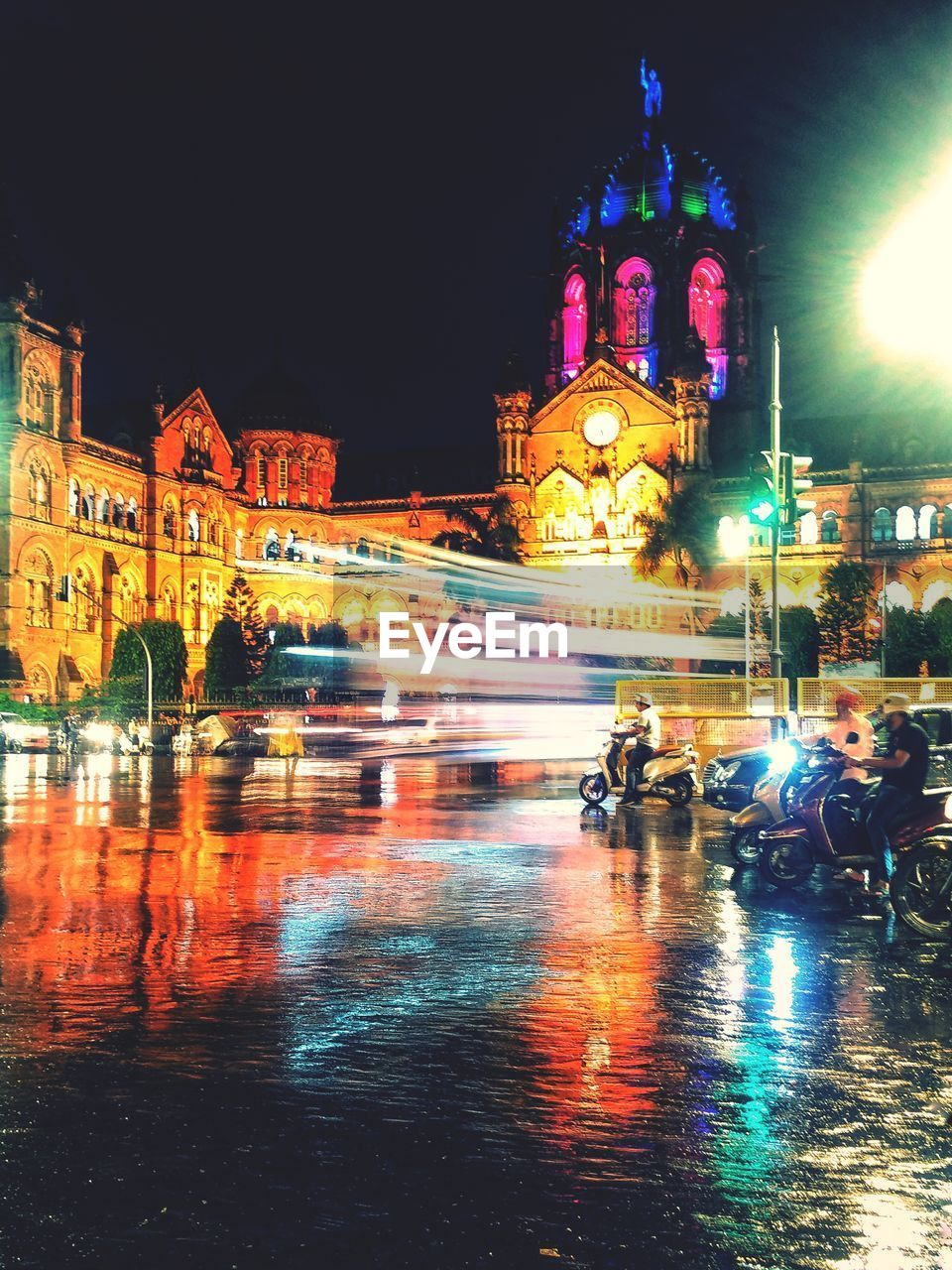 architecture, building exterior, built structure, night, illuminated, city, water, street, building, motion, blurred motion, travel, reflection, incidental people, wet, transportation, mode of transportation, travel destinations, nature, rain, outdoors