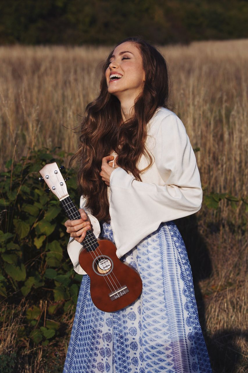 real people, one person, casual clothing, three quarter length, leisure activity, guitar, field, standing, young women, lifestyles, outdoors, beautiful woman, front view, holding, nature, young adult, day, music, musical instrument, happiness, medium-length hair, playing, smiling, grass, full length, women, musician