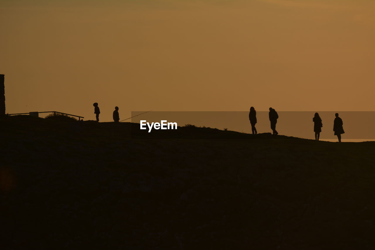 sunset, silhouette, real people, leisure activity, lifestyles, nature, walking, medium group of people, men, standing, scenics, outdoors, togetherness, landscape, vacations, beauty in nature, women, sand, sky, clear sky, beach, friendship, day, people