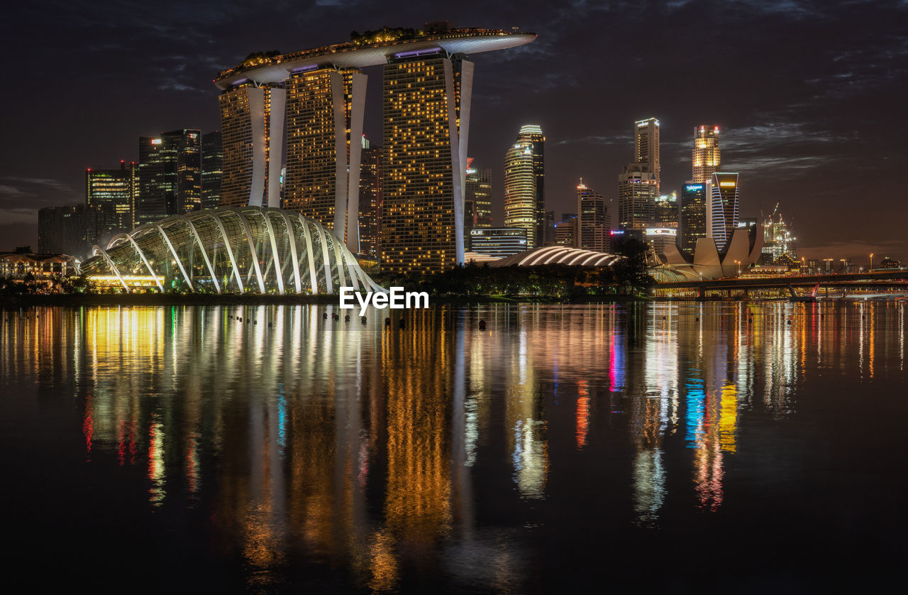 Reflection Of Modern Buildings On River At Night