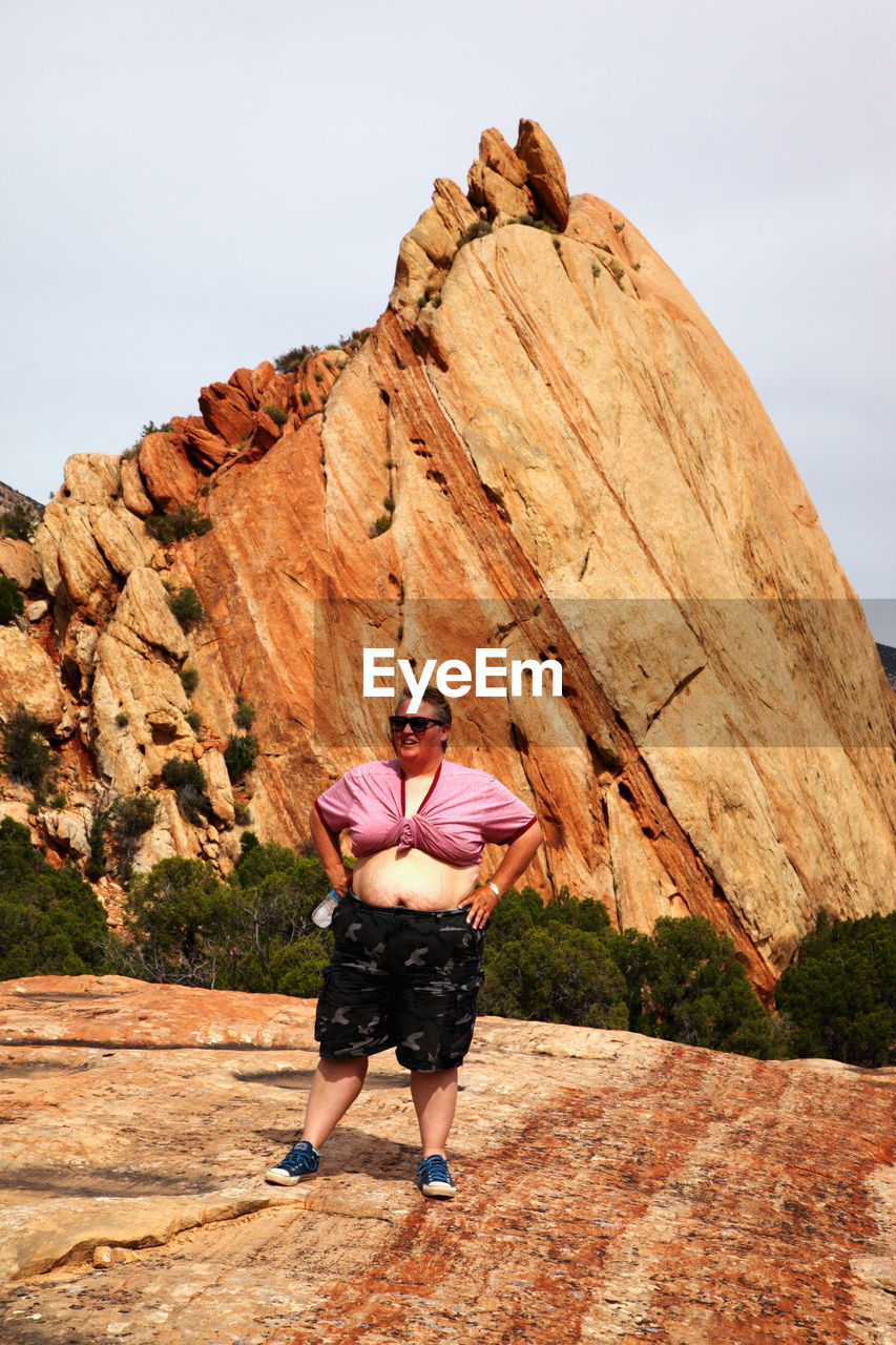 Full Length Of Mid Adult Woman Standing Against Rock Formation At National Park