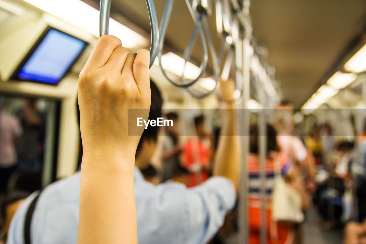 Cropped hand of woman in train