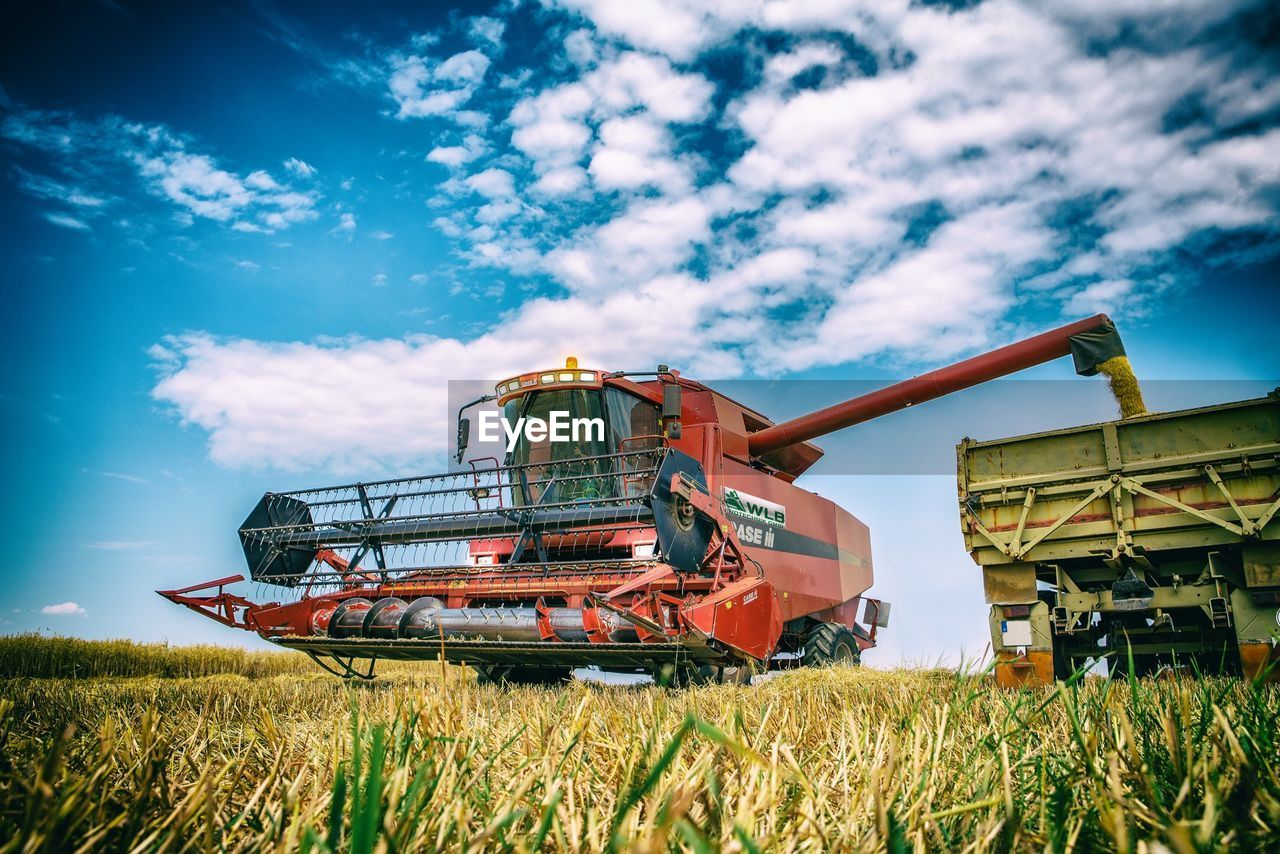 machinery, field, plant, sky, land, agriculture, agricultural machinery, day, combine harvester, nature, rural scene, landscape, cloud - sky, grass, growth, mode of transportation, crop, farm, outdoors, industry, no people