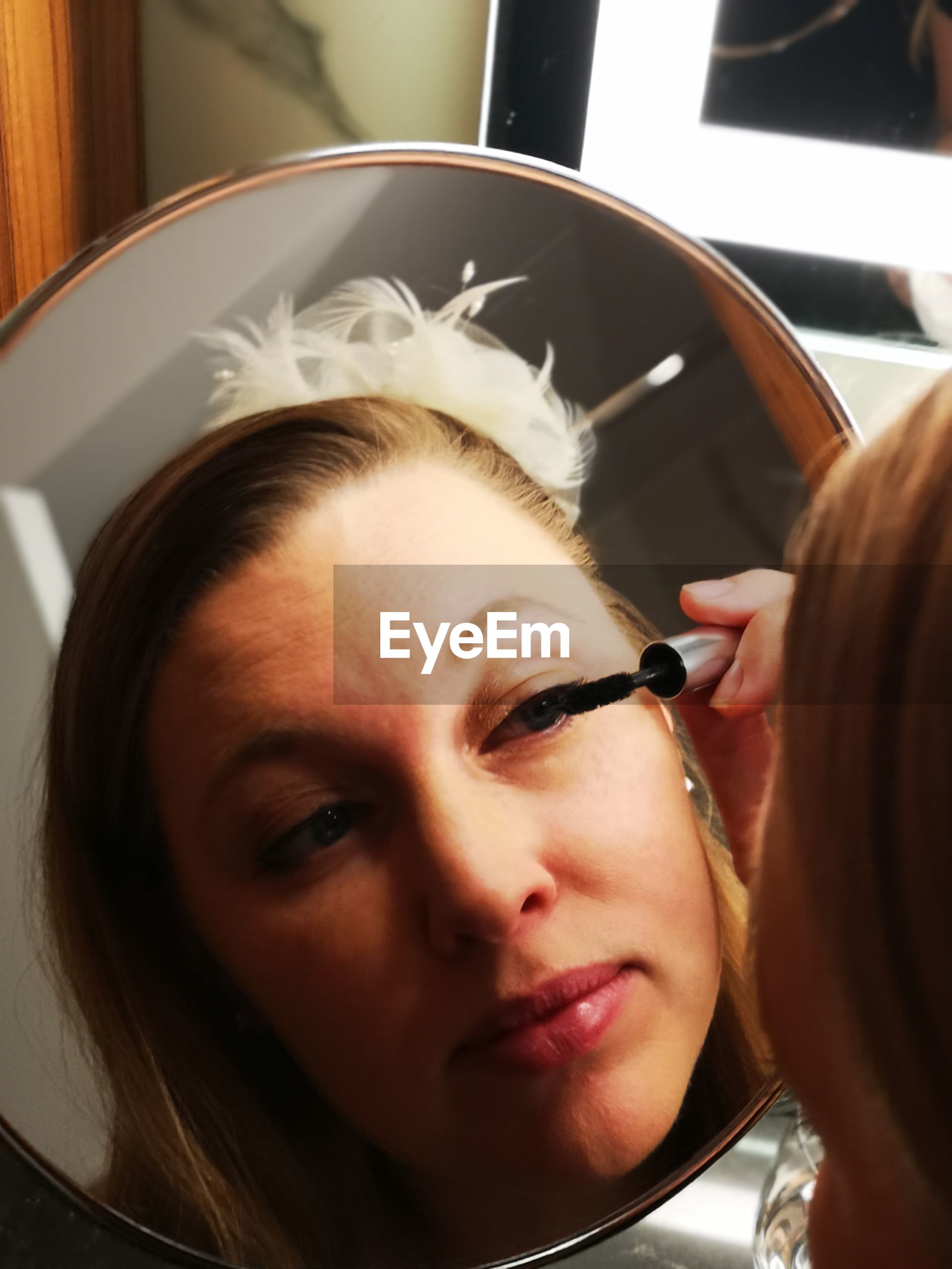 Close-up of woman applying mascara while reflecting on mirror