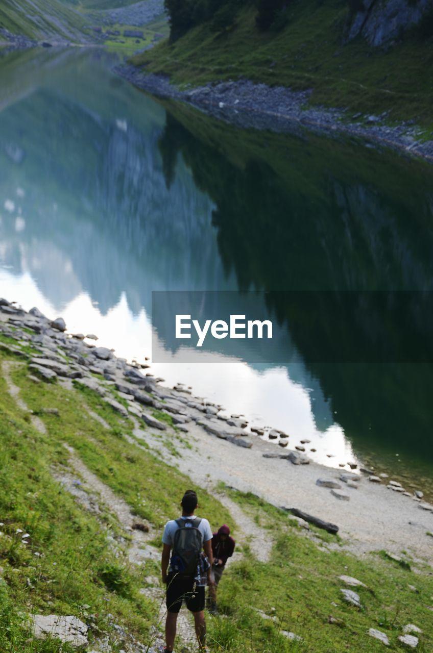 REAR VIEW OF MAN AMIDST LAKE