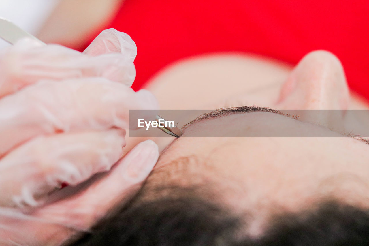 Cropped Hand Of Beautician Using Tool On Female Customer