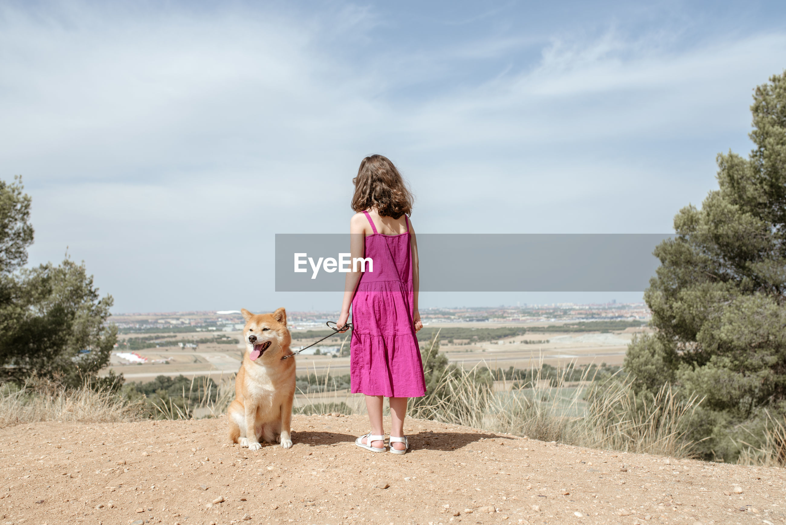 REAR VIEW OF WOMAN WITH DOG STANDING ON LAND